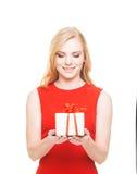 Ritratto di una donna bionda in un vestito rosso che tiene un presente Immagine Stock