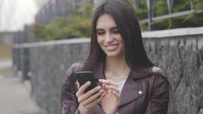 Ritratto di una donna castana che sorride e che per mezzo di uno smartphone all'aperto sulla via video d archivio