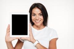 Ritratto di una donna castana sorridente che mostra la compressa dello schermo in bianco Immagine Stock