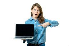 Ritratto di una donna casuale felice che mostra computer portatile in bianco s Fotografie Stock Libere da Diritti