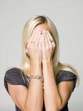 Ritratto di una donna che si nasconde in sue mani Fotografia Stock