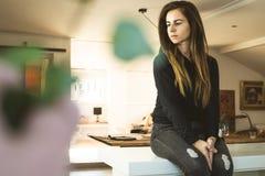 Ritratto di una donna che si siede nella cucina Donna che guarda lateralmente a casa fotografia stock libera da diritti