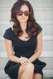 Ritratto di una donna che si siede sui punti Fotografia Stock