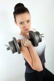 Ritratto di una donna che tiene un grande dumpbell per l'allenamento di sollevamento di peso Fotografia Stock
