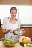 Ritratto di una donna che tiene una vaschetta della salsa Fotografia Stock