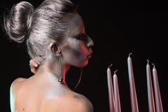 Ritratto di una donna con bodyart d'argento e l'acconciatura piacevole che tengono e che soffiano al candeliere con cinque candel Fotografia Stock Libera da Diritti