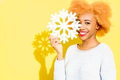 Ritratto di una donna con il fiocco di neve artificiale sui precedenti gialli Fotografie Stock Libere da Diritti