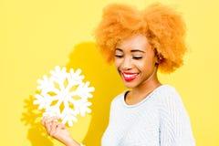 Ritratto di una donna con il fiocco di neve artificiale sui precedenti gialli Fotografia Stock