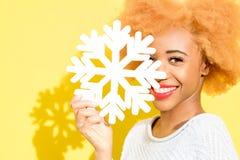 Ritratto di una donna con il fiocco di neve artificiale sui precedenti gialli Fotografie Stock