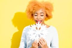 Ritratto di una donna con il fiocco di neve artificiale sui precedenti gialli Fotografia Stock Libera da Diritti