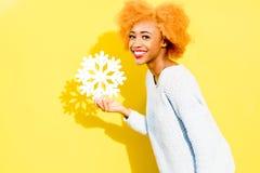 Ritratto di una donna con il fiocco di neve artificiale sui precedenti gialli Immagine Stock Libera da Diritti