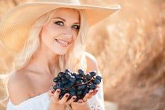 Ritratto di una donna con l'uva in mani Immagini Stock