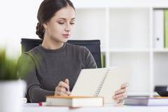 Ritratto di una donna con un libro in ufficio Immagini Stock
