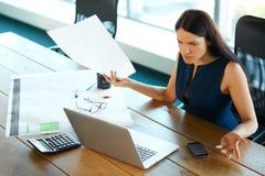 Ritratto di una donna di affari confusa che lavora con le carte dentro Fotografia Stock