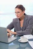 Ritratto di una donna di affari messa a fuoco che per mezzo di un computer portatile Fotografia Stock Libera da Diritti