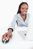 Ritratto di una donna di affari sveglia che per mezzo di un computer portatile Immagini Stock