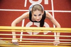 Ritratto di una donna di sport che fa allungando esercizio sullo stadio Immagini Stock