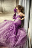Ritratto di una donna elegante in un vestito lilla con un fan Fotografia Stock Libera da Diritti