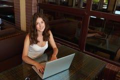 Ritratto di una donna europea splendida che posa mentre lavorando al suo computer portatile portatile durante il resto in caffett Fotografie Stock Libere da Diritti