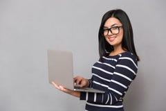 Ritratto di una donna felice che per mezzo del computer portatile Fotografia Stock Libera da Diritti
