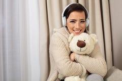Ritratto di una donna graziosa sorridente che posa con le cuffie e l'orsacchiotto fotografia stock