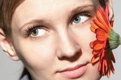 Ritratto di una donna intelligente che tiene un fiore rosso Immagine Stock Libera da Diritti