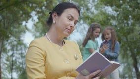 Ritratto di una donna matura elegante che legge il libro nel parco nella priorit? alta Lle cifre vaghe di due stock footage