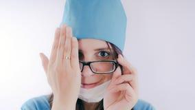 Ritratto di una donna o di un infermiere sorridente amichevole di medico in uniforme medica bianca Passi l'un occhio chiuso, il c fotografia stock libera da diritti