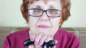 Ritratto di una donna occhialuta anziana Si siede appoggiandosi un bastone da passeggio archivi video