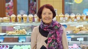 Ritratto di una donna pensionata sveglia in una drogheria nel dipartimento del pane stock footage