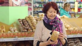 Ritratto di una donna pensionata sveglia in una drogheria nel dipartimento del pane archivi video
