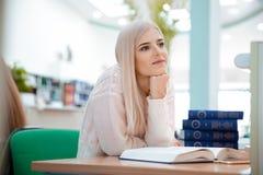 Ritratto di una donna premurosa con i libri in biblioteca Immagini Stock Libere da Diritti