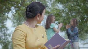 Ritratto di una donna senior elegante che legge il libro nel parco nella priorit? alta Lle cifre vaghe di due video d archivio