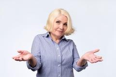 Ritratto di una donna senior piacevole che ha un gesto di dubbio fotografie stock libere da diritti