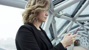 Ritratto di una donna sorridente attraente di affari in un corridoio del centro di affari facendo uso dello smartphone che chiacc archivi video
