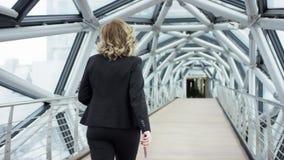 Ritratto di una donna sorridente attraente di affari in un corridoio del centro di affari facendo uso dello smartphone che chiacc stock footage