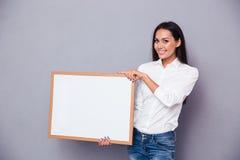 Ritratto di una donna sorridente che tiene bordo in bianco Fotografie Stock
