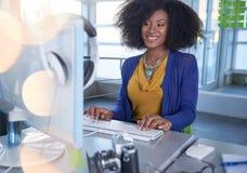 Ritratto di una donna sorridente con un afro al computer in ufficio di vetro luminoso Immagini Stock Libere da Diritti