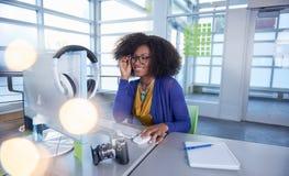Ritratto di una donna sorridente con un afro al computer in ufficio di vetro luminoso Immagine Stock Libera da Diritti