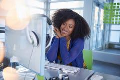 Ritratto di una donna sorridente con un afro al computer in ufficio di vetro luminoso Fotografia Stock