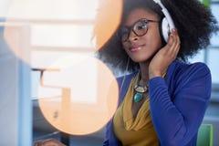 Ritratto di una donna sorridente con un afro al computer in ufficio di vetro luminoso Immagine Stock