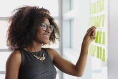 Ritratto di una donna sorridente di affari con un afro Immagine Stock