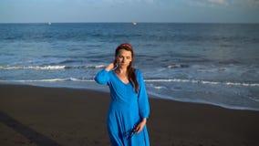 Ritratto di una donna in un bello vestito blu su una spiaggia vulcanica nera Movimento lento archivi video