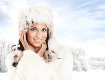 Ritratto di una donna in un cappello di inverno su un fondo soleggiato Fotografia Stock