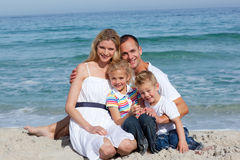 Ritratto di una famiglia allegra che si siede sulla sabbia Immagine Stock Libera da Diritti
