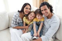 Ritratto di una famiglia sorridente che si siede sul sofà immagini stock