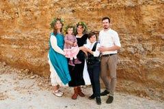 Ritratto di una famiglia di tre generazioni in retro vestiti rustici d'annata e corone contro un fondo della parete di giallo sab Fotografia Stock