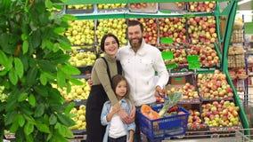 Ritratto di una famiglia in un supermercato sui precedenti degli scaffali con le mele archivi video