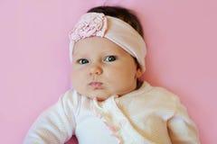 Ritratto di una fascia d'uso e di riposarsi del fiore del pizzo della neonata sveglia di due mesi sulla coperta rosa Fotografie Stock