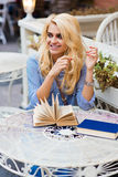 Ritratto di una femmina felice della donna con il bello sorriso che si siede con i manuali in caffetteria all'aperto prima delle  Immagine Stock
